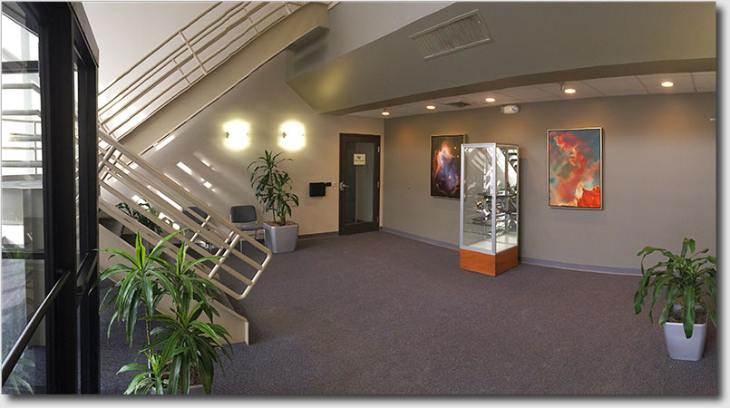 Images of bright, sunny foyer; loading dock, recycling zone, landscaped entrance; and nearby Lake Nagog